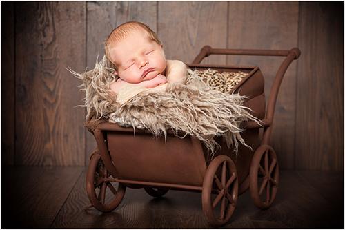 Neugeborenenfotografie Düsseldorf. Baby schläft auf hinteren Rand des Kinderwagens gelehnt.