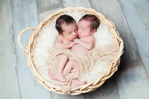 Fotografie Neugeborene Düsseldorf: Baby-Zwillinge liegen in weißer Decke aneinandergekuschelt in Körbchen und schlafen.