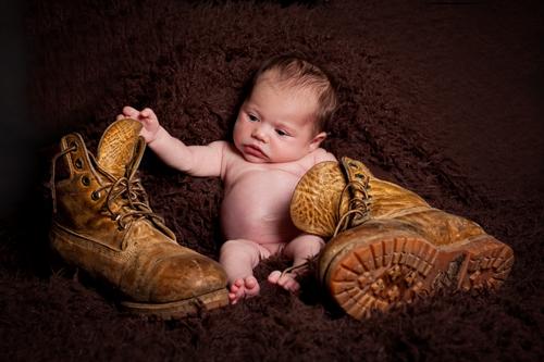 Fotografin Neugeborene Düsseldorf: Baby sitzt zwischen zwei alten Wanderstiefeln und spielt damit.