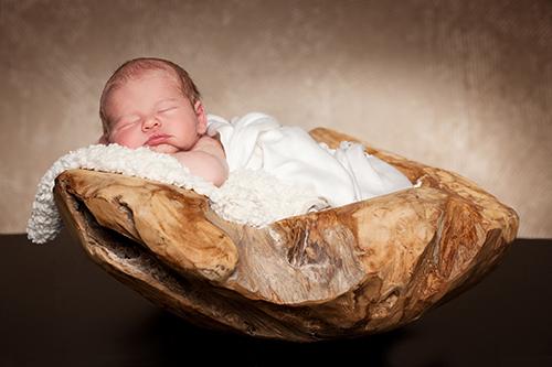 Neugeborenenfotos Düsseldorf: Baby in weißer Wolldecke liegt in einer dicken Holzschale vor braunem Hintergrund.