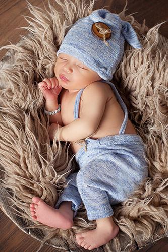 Babyfotos Düsseldorf: Baby mit blauer Hose und blauer Mütze liegt seitlich auf brauner Zottel-Wolldecke
