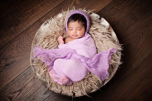 Fotostudio Baby Duesseldorf: Baby mit pechschwarzem Haar schkummert in lila Tuch gewickelt in einer mit Wolldecke ausgelegten Holzschale