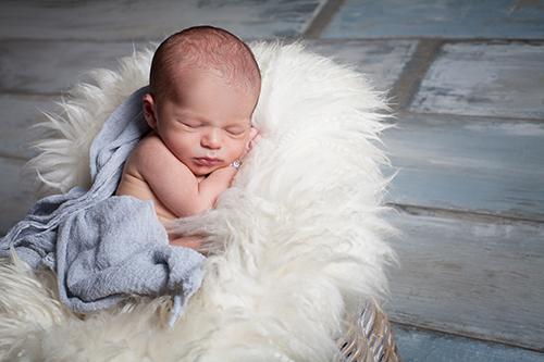 Fotograf Baby Düsseldorf: Neugeborenes schläft in weichem Schafsfell
