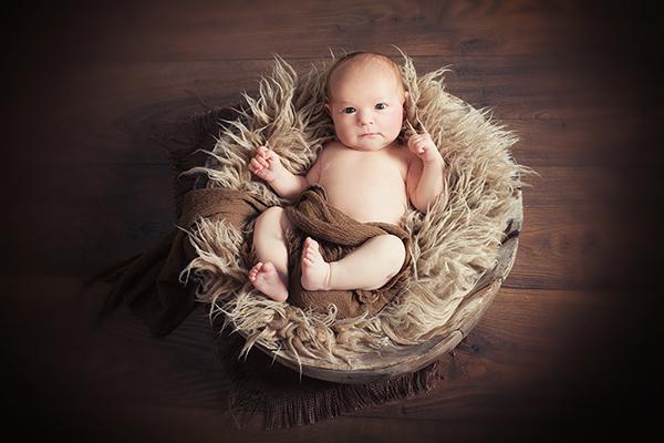 Babyfotografin Düsseldorf fotografiert Baby von oben. Das baby liegt in Holzschale und beobachtet mit wachem Blick das Geschehen.
