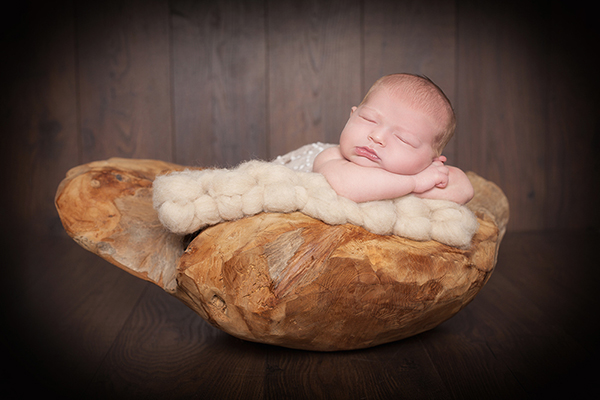 Newbornshooting Düsseldorf: Neugeborenes schläft in Holzschale. Neugeborenenfotografin A. Ola Karlowski