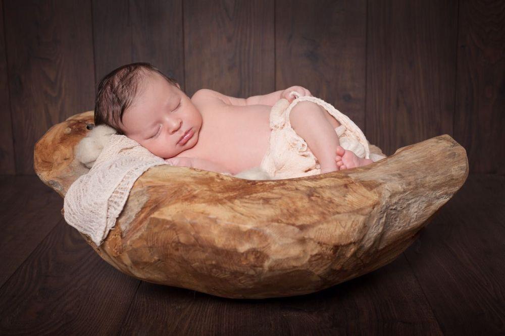 Fotograf für Babys Düsseldorf. Baby schläft in Holzschale.