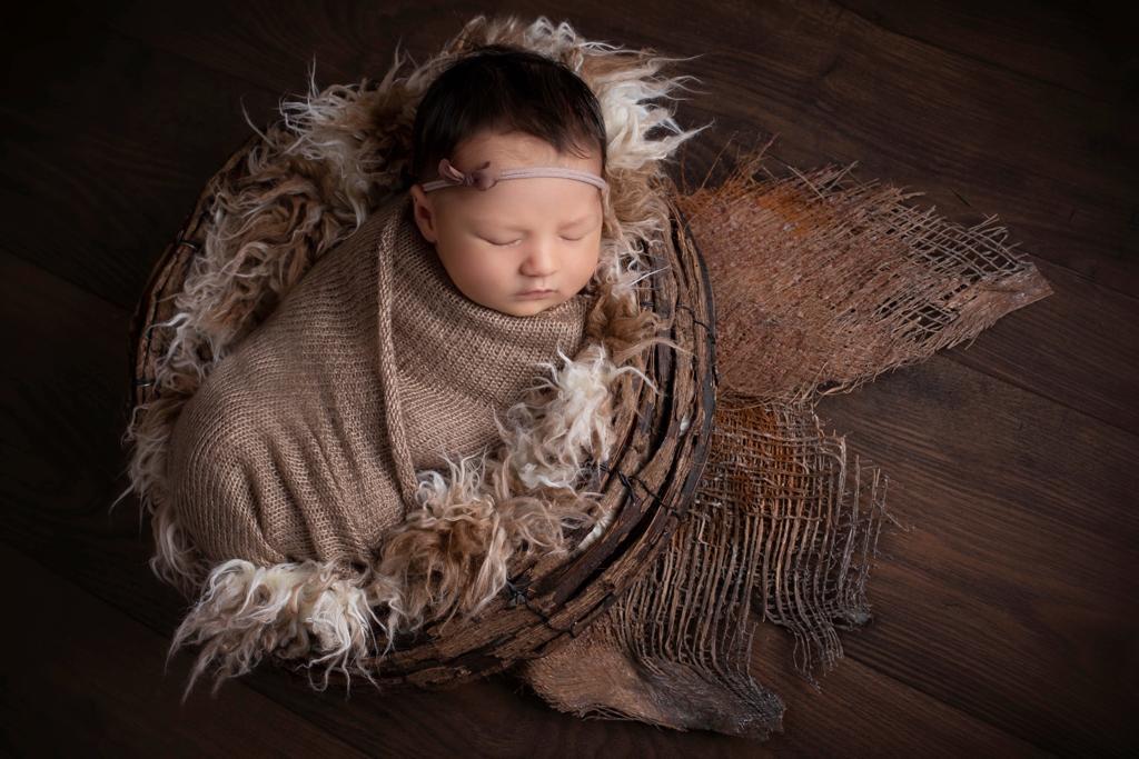 Babyfoto Düsseldorf: Baby liegt kuschelig gewickelt in einem Fell in einer Weidenschale. Herbststimmung.