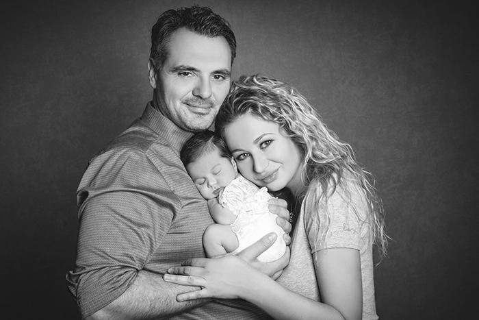 Babyfotografin Düsseldorf: Die beiden Eltern stehen mit ihrem Baby kuschelnd glücklich in die Kamera schauend