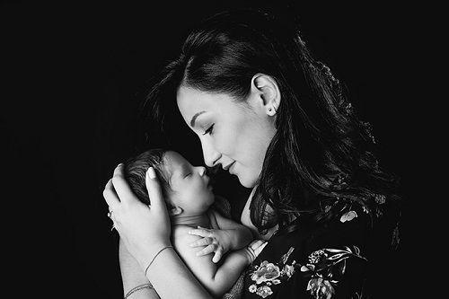 Baby Fotografin Düsseldorf: Junge Mutter hält das Näschen ihres kleinen Babys direkt vor die eigene Nase und hält das Kleine dabei zärtlich in den Händen.