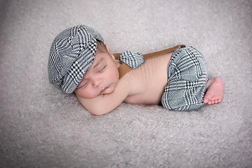 Neugeborenenfotografie Düsseldorf. Babyfotografie Düsseldorf. Baby liegt mit Bauch auf weicher Decke