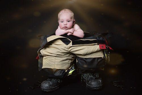 Fotoshooting mit Baby in Düsseldorf, das auf einer Feuerwehrausrüstung posiert