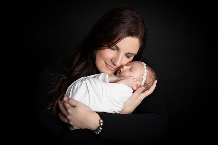 Newbornshooting Düsseldorf: Mama hält verliebt ihr Neugeborenes in den Armen und schmiegt mit geschlossenen Augen ihren Kopf an das Baby.